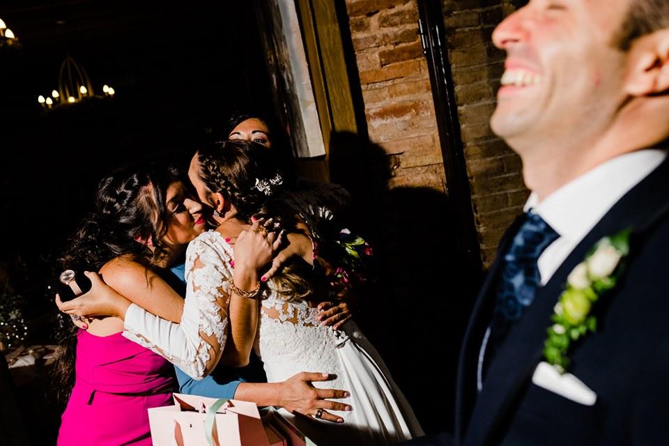 Novio riendo mientras novia abraza a sus amigas con un regalo - Fotógrafo de bodas Ciudad Real - David Copado
